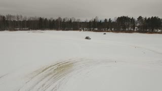 Winter off-road racing side-by-side vehicles. Aerial view: Rally on the buggy on the snow on a winter day. Racing in the SXS class. Buggy, sports car on rally. Off Road Series racing. 4K video, drone