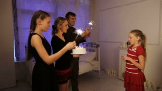 Young girl is blowing out candles on cake. Girl blows out the candles on birthday cake with lots of candles. Happy family celebrating a birthday