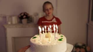 Young girl is blowing out candles on cake. Girl blows out the candles on birthday cake with lots of candles