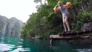 Young girl jump to a warm summer lake.Little girl leaps off the end of the dock into mountain lake.Slow motion.Travel concept.Family,summer vacation