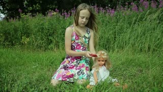 Young girl playing with doll on outside grass.young girl in beautiful dress sitting on the grass and playing with a doll on a summer day behind the girl flowers combs doll hair.