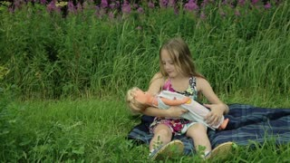 Young girl playing with doll on outside grass.young girl sitting on the grass and playing with a doll on a summer day behind the girl res flowers