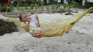 Young girl relaxing on hammock and using digital tablet. girl lies in a hammock on a tropical beach and playing with a digital tablet. Travel concept. Family,summer vacation. Happy family