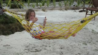 Young girl relaxing on hammock and using digital tablet.girl lies in a hammock on a tropical beach and playing with a digital tablet.Travel concept.Family,summer vacation.Happy family