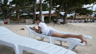 Young girl relaxing on the beach and using digital tablet.Travel concept.Family,summer vacation.Happy family