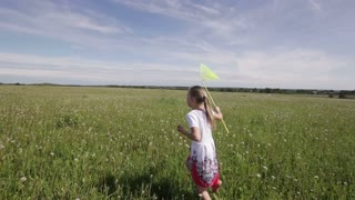 Young girl running with butterfly net.funny girl are playing in field. butterfly net catch butterflies,camera is stabilized on  steadicam.