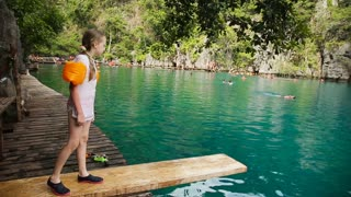 Young girl runs down the dock to jump to a warm summer lake.Little girl leaps off the end of the dock into mountain lake.Travel concept.Family,summer vacation.