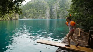 Young girl runs down the dock to jump to a warm summer lake.Little girl leaps off the end of the dock into mountain lake.Travel concept.Family,summer vacation