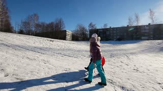 Young girls with plastic sled up the hill in winter, sunny day.Happy girl expressing joy while sledding in the snow in the winter.Outdoor winter fun for family.nice winter scene.steadicam scene