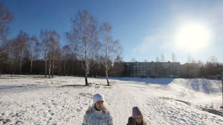 Young girls with plastic sled walking in the park in winter, sunny day.Happy girl expressing joy while sledding in the snow in the winter.Outdoor winter fun for family.nice winter scene.steadicam