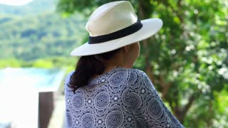 00:09 Asian woman enjoy herself in hot tropical nature holiday wearing summer hat