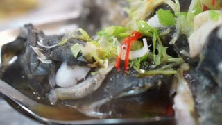Asian Chinese style whole fish steamed with soy sauce and spring onion topping
