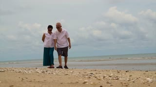 Asian elderly couple collecting shells on the beach