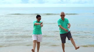 Asian elderly couple doing small exercise at sea beach