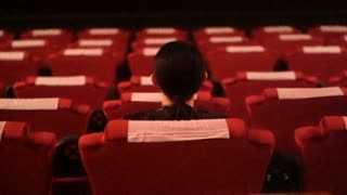 Asian ethnic girl sitting alone in empty red seat cinema theater