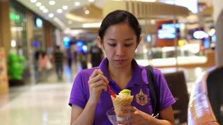 Asian girl eating ice cream in department store short