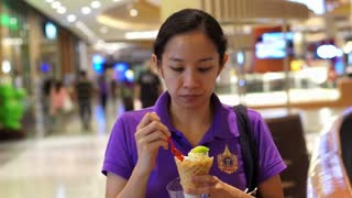 Asian girl eating ice cream in department store