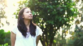 Asian girl in green nature background smiling Slow motion