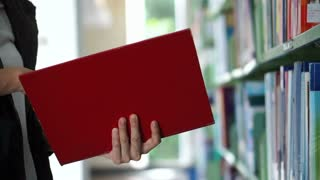 Asian girl looking for book, flip through and put back on library shelves