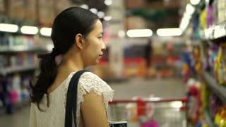 Asian girl selects items in hypermarket, supermarket shelves