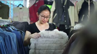 asian girl shopping and looking cloth seriously in second hand shop