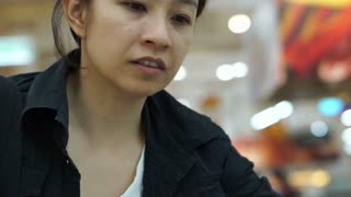 Asian girl shopping in supermarket picking frozen food for home gorcery