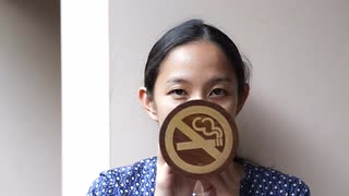 Asian girl with no smoke sign cover her mouth