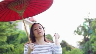 Asian girl with red oriental style umbrella on green nature background