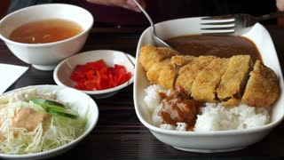 Asian guy eating Japanese curry with tonkatsu, fried pork in food lunch set