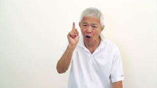 Asian man Senior looks at camera shakes head and do hand gesture to decline, says no