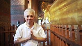Asian man senior tourist visit Sleeping Buddha, Reclining Buddha statue in Wat Pho of Bangkok, Thailand