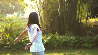 Asian mixed race girl happily turn around and smile in morning nature background