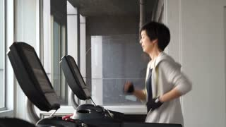 Asian mixed race sporty woman finish jogging on treadmill in gym, done for the day