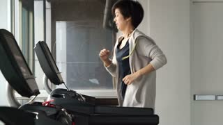 Asian mixed race sporty woman jogging on treadmill in gym, exercise and fitness concept