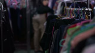 Asian mixed race woman shopping second clothes at flea market warehouse