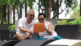 Asian retired senior couple using pad at pool side during holiday fun trip