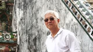 Asian retired senior man travel to Thailand, visiting temple in Bangkok