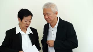 Asian senior businessman and business woman looking at report with unhappy expression