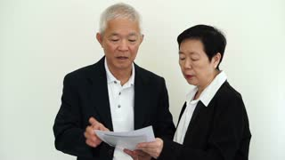 Asian senior businessman and businesswoman executive reading report with happy expression