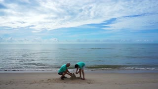Asian senior couple building decorating sand castle at the beach. Abstract life contribution