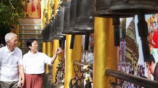 Asian senior couple doing ritual bell ringing in Buddhist temple believe for good luck