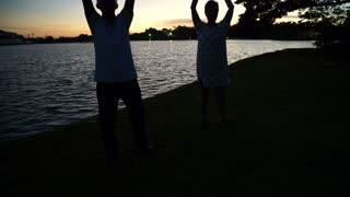 Asian senior couple exercise together at morning dawn lake