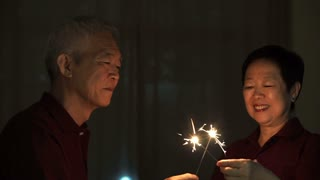 Asian senior couple playing firework, sparklers, fire cracker at night. Concept celebrating life