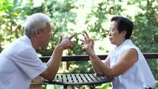 Asian senior couple playing hand game to practise their brain in nature background