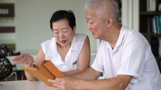 Asian senior couple reading news together from tablet in small library. Learning and study concept