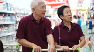 asian senior couple shopping at supermarket with cart