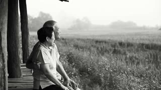 Asian senior couple sitting in the gazebo next to rice field. Farm and agricultural business black and white