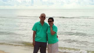 Asian senior couple stand at the beach at looking to ocean