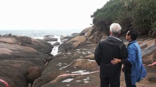Asian senior couple travel together smiling and looking at camera happily