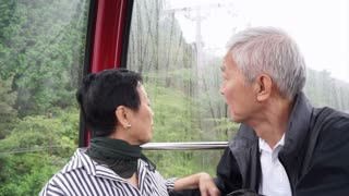 Asian senior couple traveling on ropeway cable car up in the mountain for retirement trip